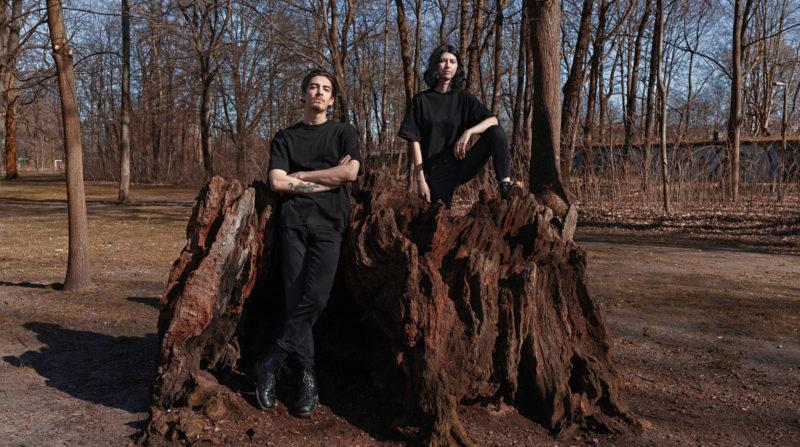 Zwei Menschen stehen an einem Baumstumpf